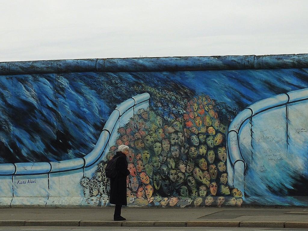 Bild von Berlin Wall. road street city blue sky people black berlin art history wall germany painting graffiti freedom europe faces pavement figure metropolis