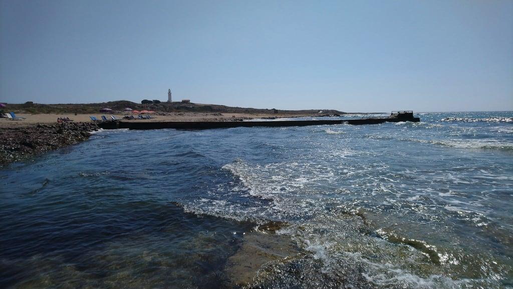 Bild av Lighthouse Beach. mesesettembre faro mare baia spiaggia sabbia scogli acqua cielo panorama natura costa insenatura